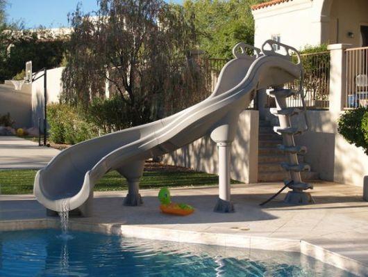 Escorregador para piscina de fibra grande com algumas curvas em suas extensão e uma escada com degraus criativos.