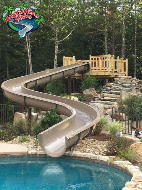 Escorregador para piscina de fibra extenso e sinuoso que pode ser acessada por uma escada de pedras.