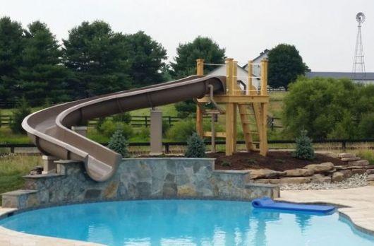 Escorregador para piscina alto com uma curva ingrime que pode ser acessado por uma plataforma de madeira alta.