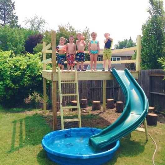 Crianças em uma plataforma de madeira onde há um pequeno escorregador que vai até uma pequena piscina de plástico.