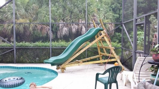 Foto de um escorregador para piscina com a parte de escorregar feita com fibra e a base / escada de madeira.