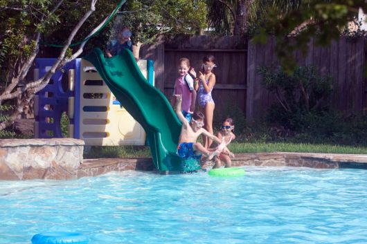 Crianças brincando na beira da piscina onde há um escorregador pequeno de plástico.