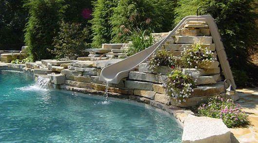 Foto de um escorregador para piscina em forma sinuosa entre pedras rústicas.