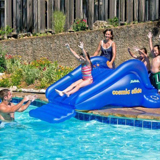 Família em volta de um escorregador para piscina inflável enquanto uma menina escorrega para cair na água.