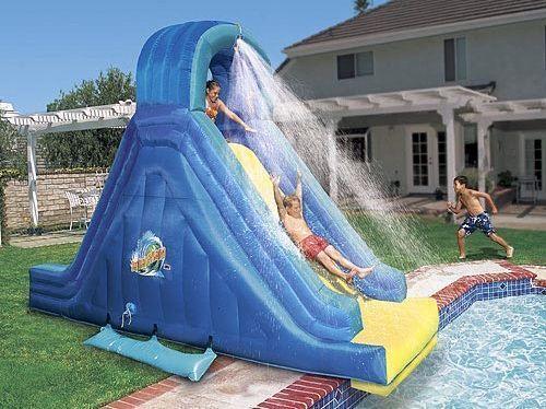 Escorregador para piscina inflável alto com uma descida ingrime. Há uma mangueira no topo que espalha água em quem está descendo.