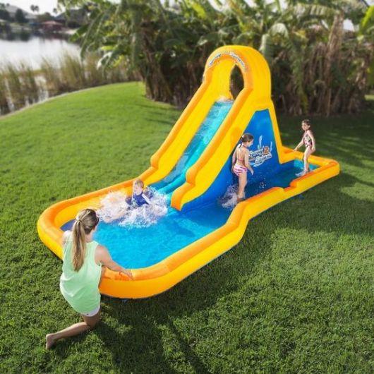 Crianças brincando em uma piscina inflável que tem um escorregador agregado a ela.