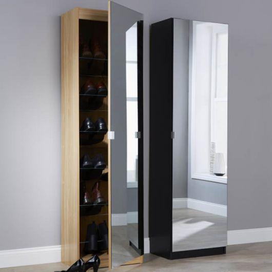 Sapateira de madeira alta fina. Ela tem vários andares onde os calçados podem ser posicionados e conta com um espelho na parte externa da porta.