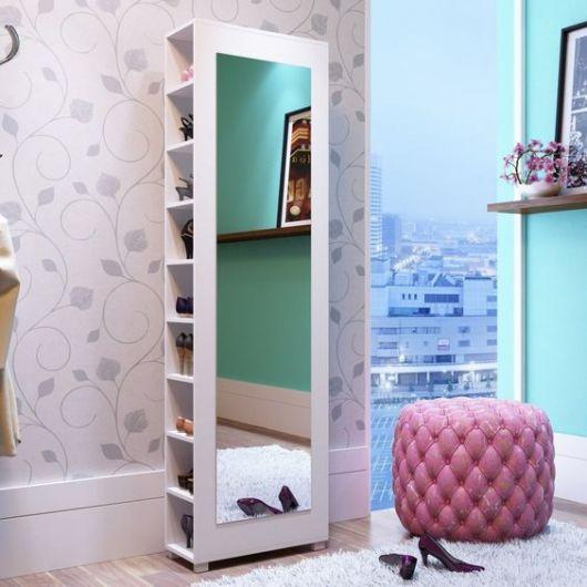Sapateira de madeira alta em um quarto feminino. O espelho fica na lateral da sapateira e cobre da cabeça aos pés de quem se olha nele.