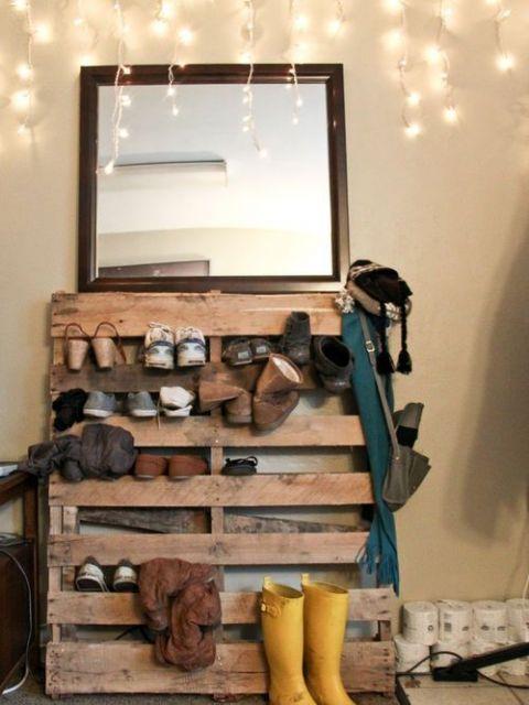 Sapateira de madeira feita com pallets. Logo acima dela há um espelho posicionado na parede.