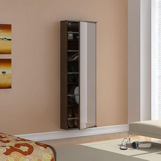 Sapateira de madeira instalada na parede com um espelho grande na parte externa da porta.