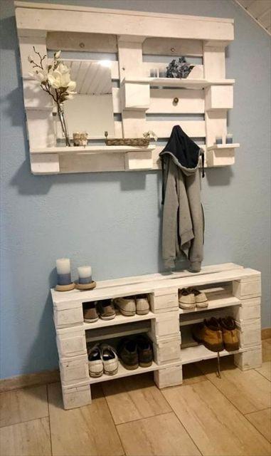 Sapateira de madeira branca baixa com quatro divisões para guardar os sapatos. Acima dela há um espelho com pequenas estantes onde são posicionados objetos decorativos.