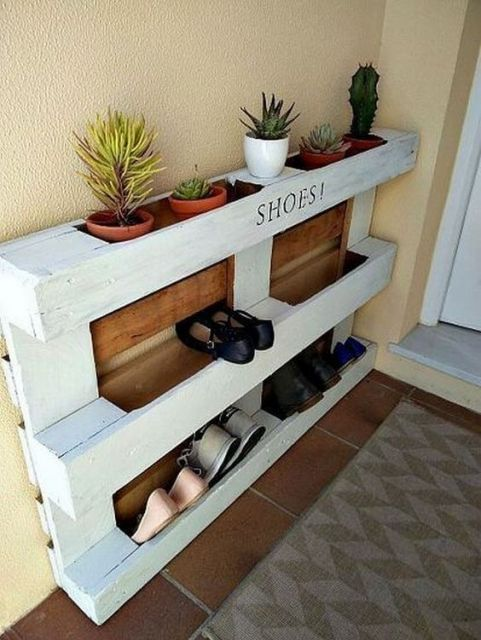 Sapateira de madeira branca instalada diretamente na parede.  Ela é feita a partir de uma caixa de pallets e os sapatos são posicionados verticalmente entre as madeiras.