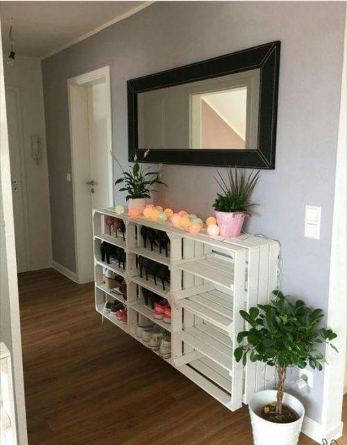 Sapateira de madeira branca grande espaçosa instalada na parede ao lado da porta de uma casa. O topo dela serve como bancada para objetos de decoração como luzes e vasos.