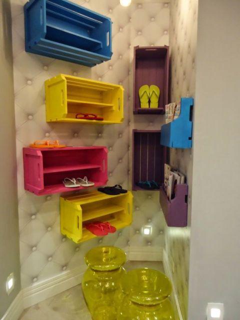 Diversas sapateiras artesanais instaladas na parede, cada um com cor diferente da outra. Elas são feita com caixas de feira.