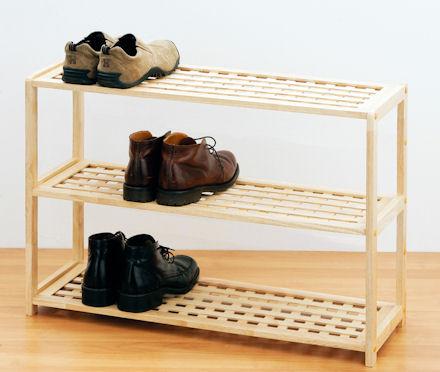 Sapateira de madeira pequena com três níveis e um par de sapatos posicionado em cada um deles.