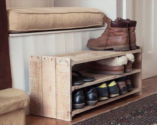 Sapateira de madeira pequena com alguns pares de sapato. Ela é feita a partir de um caixote está do lado de uma cama.
