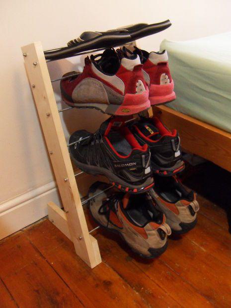 Sapateira de madeira pequena em formato vertical que suporte três pares de sapato. Ela está do lado de uma cama.