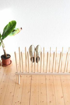 Sapateira de madeira pequena feita a partir de uma madeira redonda horizontal e diversos espetos verticais que suportam o sapato pelos furos onde entram os pés.