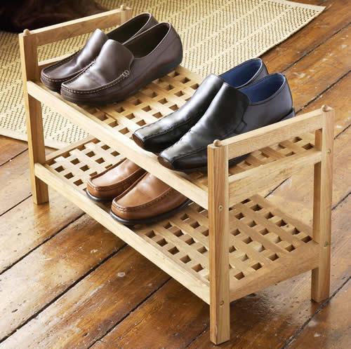 Sapateira de madeira pequena com dois níveis para que os sapatos sejam guardados e uma pequena alça lateral para facilitar sua locomoção.