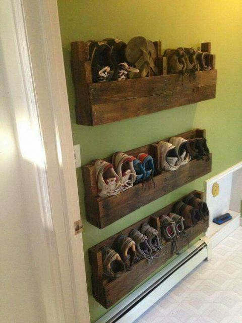 Sapateira de madeira instalada diretamente na parede. Ela é feita com madeiras pregadas umas nas outra e os sapatos ficam em posição vertical dentro da madeira.