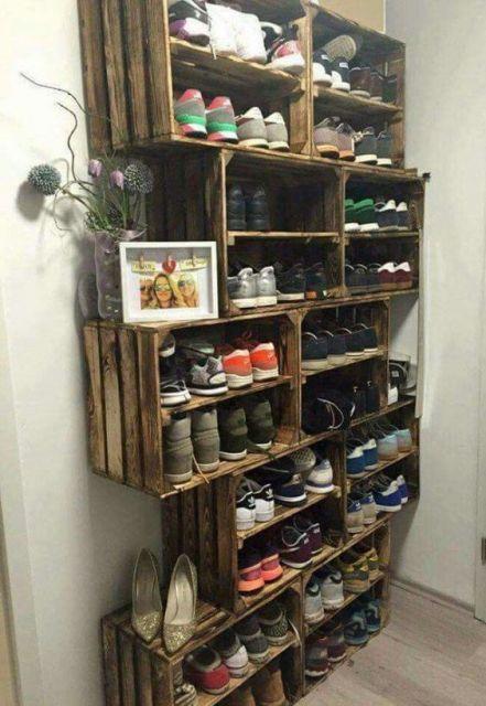 Sapateira de madeira enorme que cobre verticalmente uma parede. Ela é feita com caixas de pallets e tem muitos pares de sapatos dentro dela.