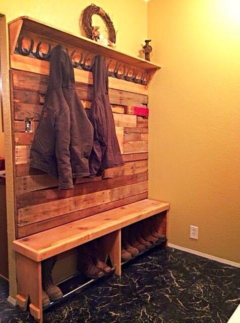 Móvel de madeira com ferraduras na parte superior que servem para guardar casados e uma sapateira na parte inferior abaixo de um banco.