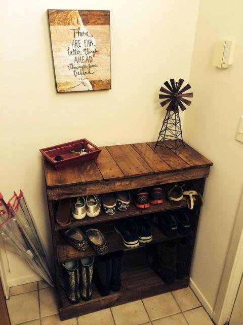 Sapateira de madeira com três níveis e uma bancada no topo, onde estão posicionados alguns objetos decorativos.