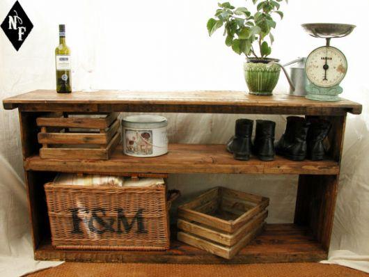 Rack de madeira com um espaço para guardar sapatos que fica abaixo de uma bancada onde estão alguns objetos decorativos.