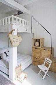 Cama com escada feita com gavetas de madeira.
