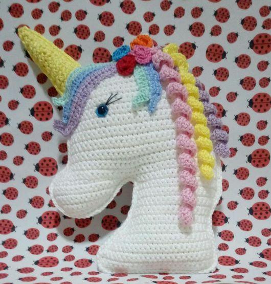 Almofada de croche de unicornio nas cores, branco, azul, rosa e amarelo claro.