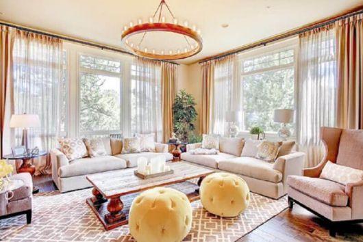 Sala clean com janelas amplas e puffs amarelos redondos.
