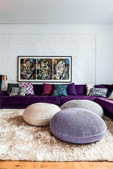 Sala ampla com sofá roxo, paredes brancas e puffs de tricot.