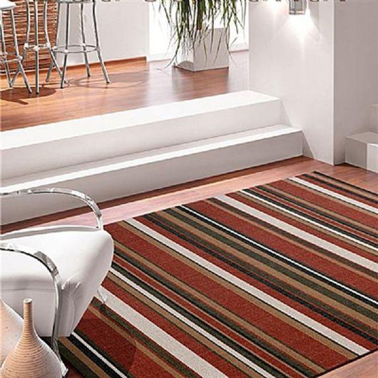 Sala clean com escadas brancas e tapete colorido grande.
