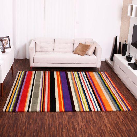 Modelo de sala branca com sofá branquinho, almofadas e tapete colorido.
