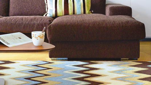 Sala com sofa marrom escuro e tapete azul com marrom e amarelo.