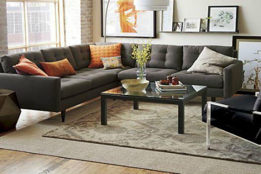 Sala moderna com sofá preto e tapete estampado.