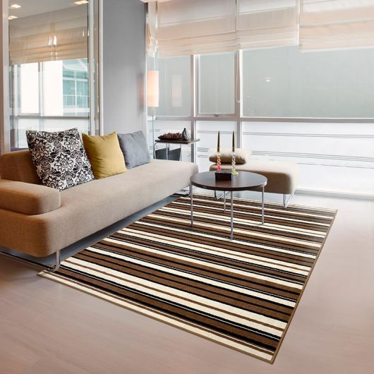 Sala branca com janelas de vidro, sofá cinza claro e tapete de listras marrom e amarelinho.