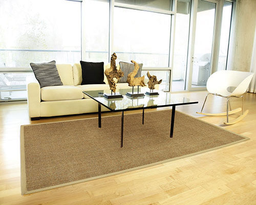 Modelo de sala com janelas amplas de vidro, sofá amarelo claro, mesa de centro e tapete sisal.