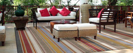 Sala pequena com sofá de vime e tapete sisal colorido em azul,verde musgo, nude e vermelho.