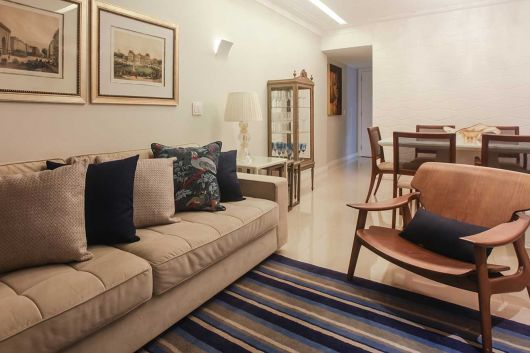 Sala branca com sofá claro e tapete sisal azul listrado.