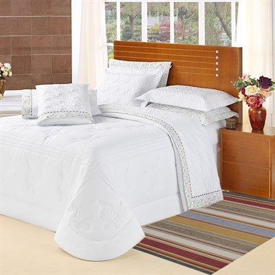 Quarto com cama de casal ampla clean com tapete sisal colorido.