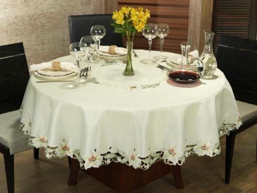 Toalha de mesa cor nude com babados de flores.