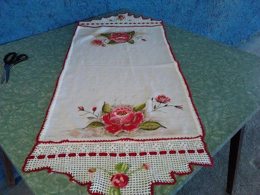 Bico de crochê em caminho de mesa branco com flores pintadas