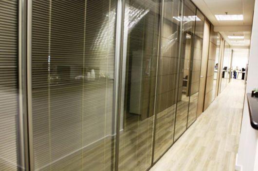 Divisória de vidro para escritório com persiana.