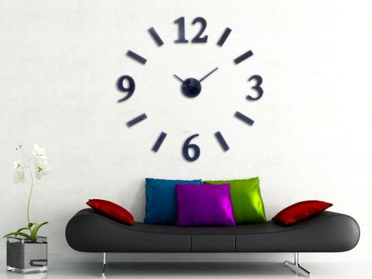 sala branca com sofa preto e almofadas coloridas e relogio de parede preto.