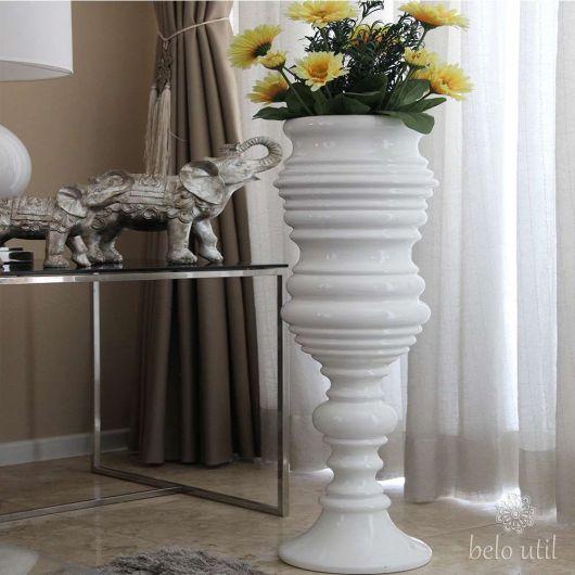 Vaso de plantas branco com flores amarelas.