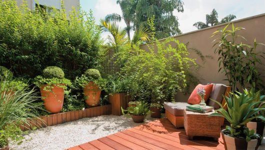 varanda com plantas em tons verdes e estofado.