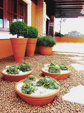 jardim térreo com vasos de chao baixos em tons laranja.