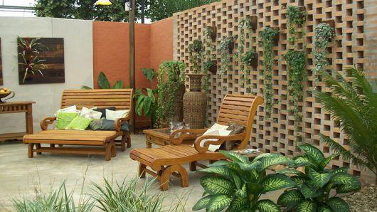 jardim com cadeiras marrom e plantas em parede vertical.