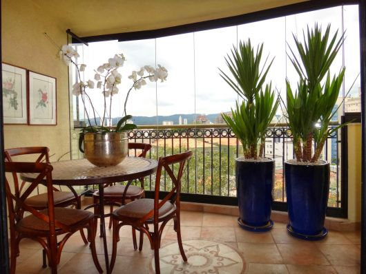 vasos de plantas azuis em varanda sacada com mesa.